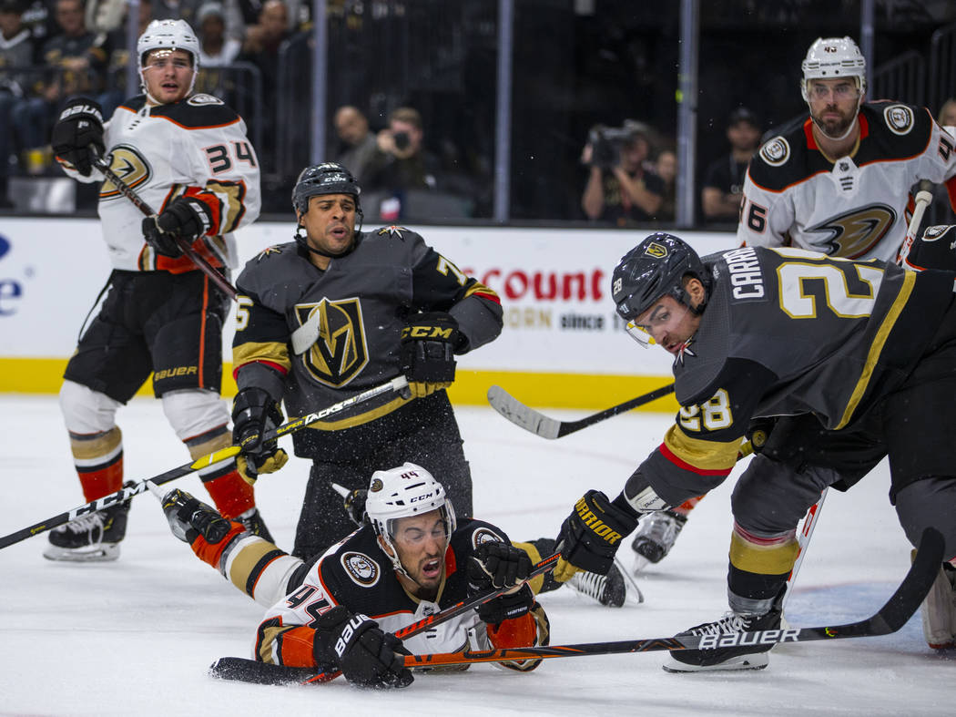 Vegas Golden Knights left wing William Carrier (28, right) looks to the puck after taking down ...