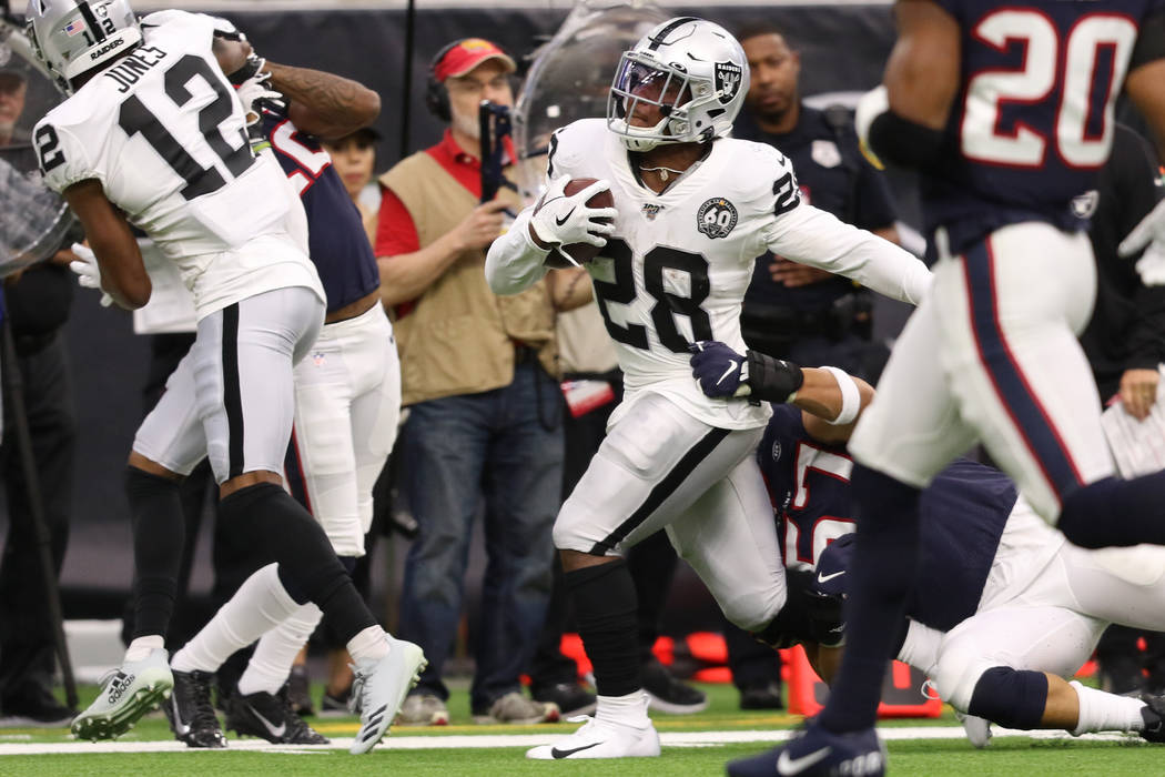 Oakland Raiders running back Josh Jacobs (28) tries to shed a tackle from Houston Texans outsid ...