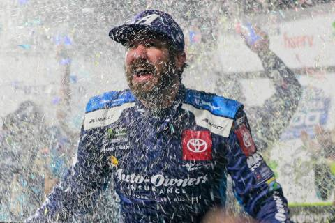 Martin Truex Jr. is doused with water and confetti after winning a NASCAR Cup Series race at Ma ...