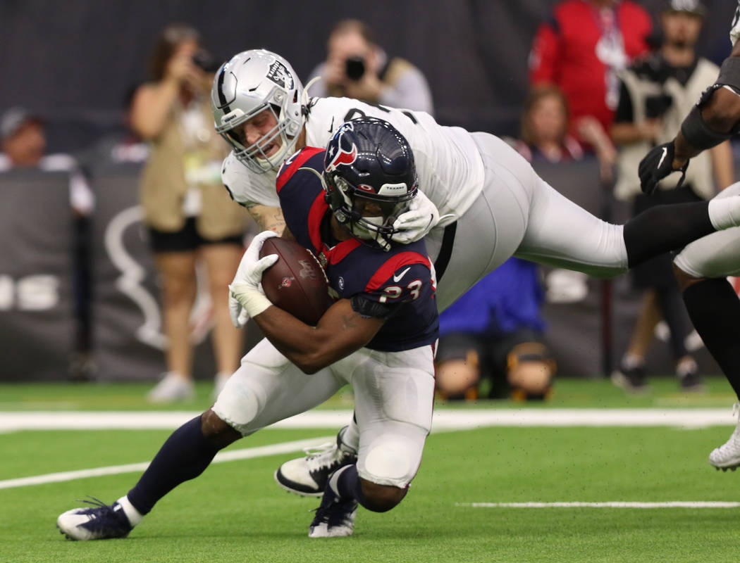 Oakland Raiders defensive end Maxx Crosby (98) grabs the facemask of Houston Texans running bac ...