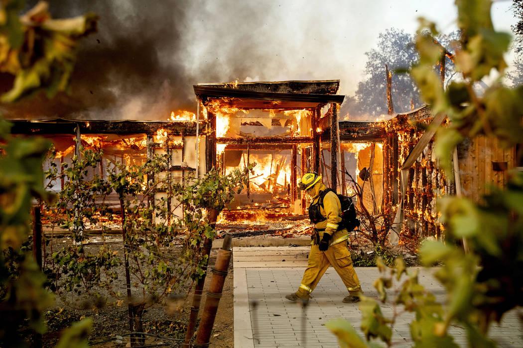 Woodbridge firefighter Joe Zurilgen passes a burning home as the Kincade Fire rages in Healdsbu ...