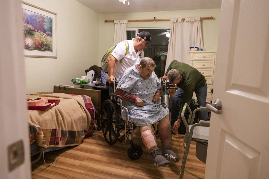 Henry Provencher, center, 87, receives help from his son Henry Provencher, left, and Eric Moess ...