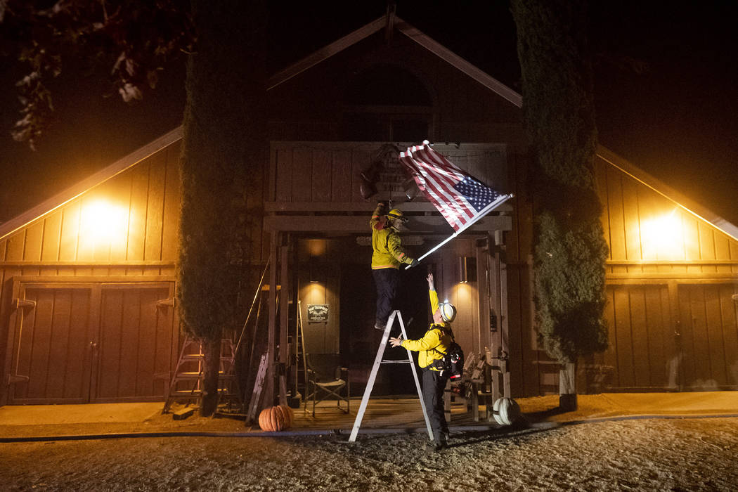 Firefighters from Dry Creek Rancheria remove an American flag as the Kincade Fire bears down on ...