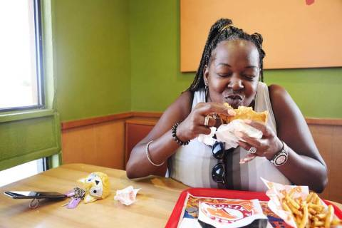 Janine Blake rejoices after have another bite of the new spicy chicken sandwich at Popeyes, Aug ...