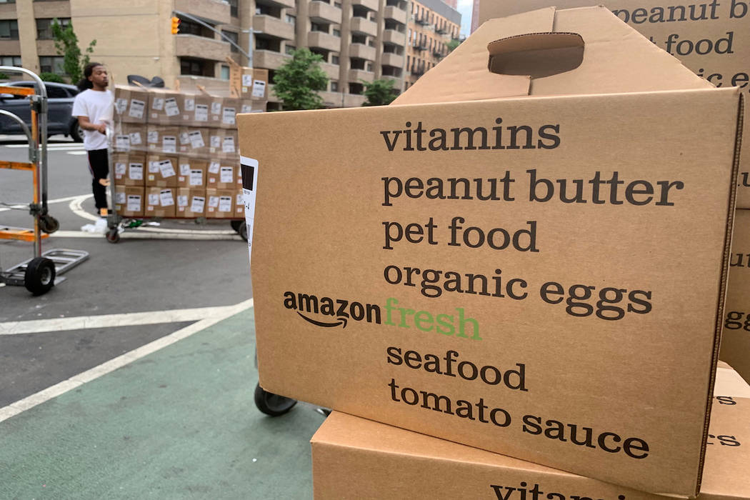In this Sunday, June 16, 2019, photo, boxes of Amazon Fresh deliveries are unloaded. (AP Photo/ ...