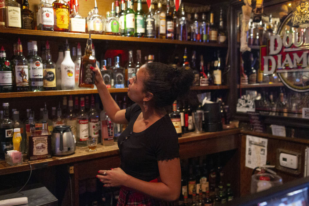 Bartender Lindsey Cruz pours a drink while sharing her experience with the supernatural earlier ...