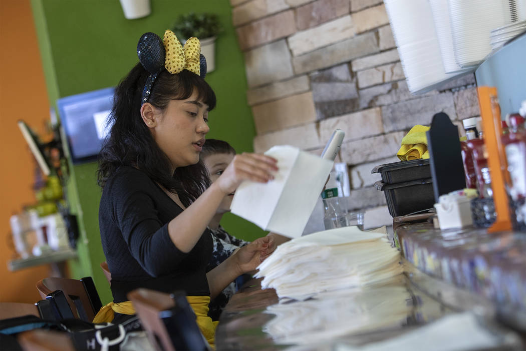 Mikayla Cabildo of Chicago, dressed as Minnie Mouse, rolls silverware at Rise & Shine in the So ...