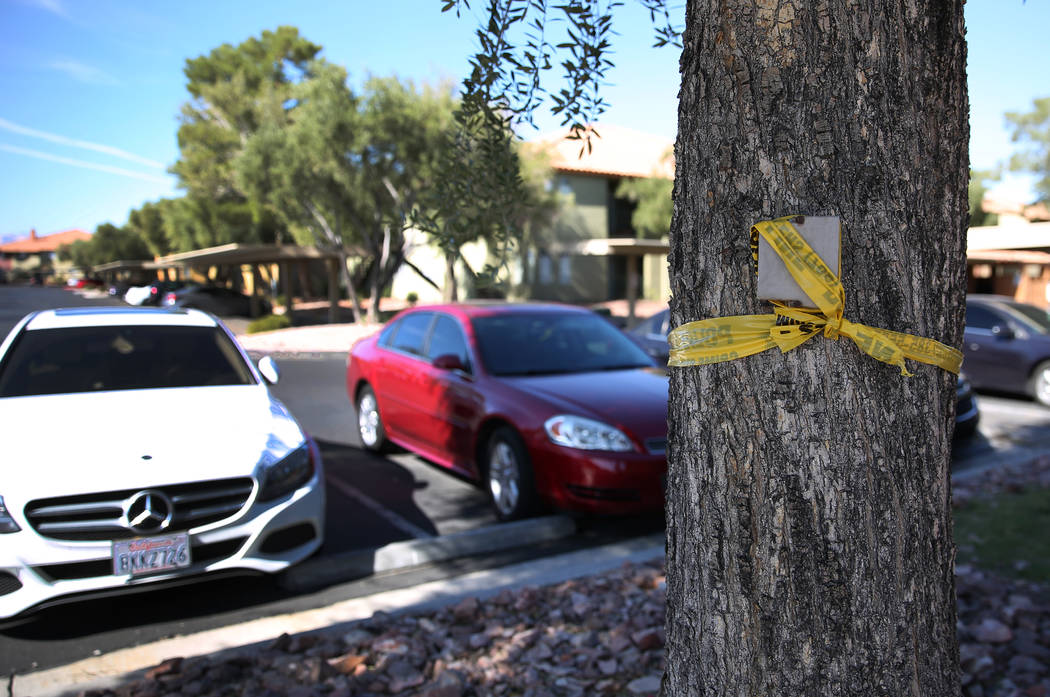 A portion of yellow police tape marks the crime scene at the Indian Hills Apartments complex at ...