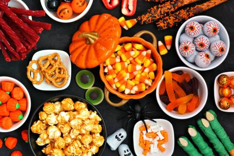 Halloween candy buffet table scene over a black stone background. Assortment of sweet, spooky t ...