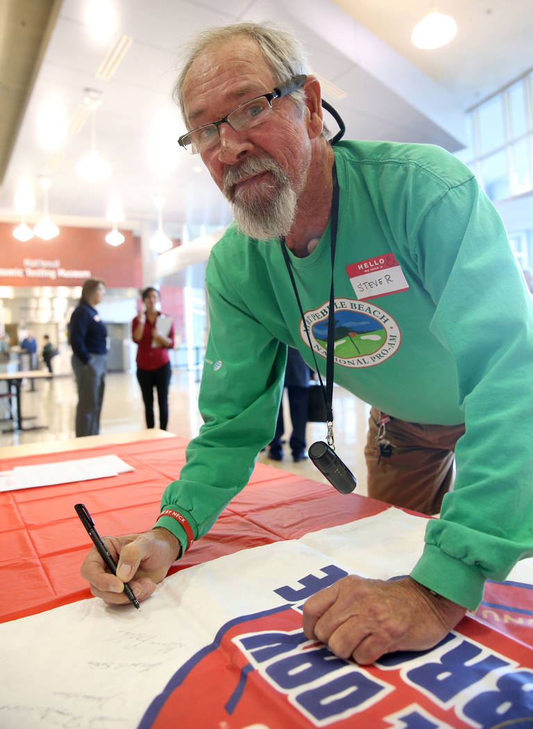 Steve Radley, 73, of Pahrump signs a banner during the Cold War Patriots National Day of Rememb ...