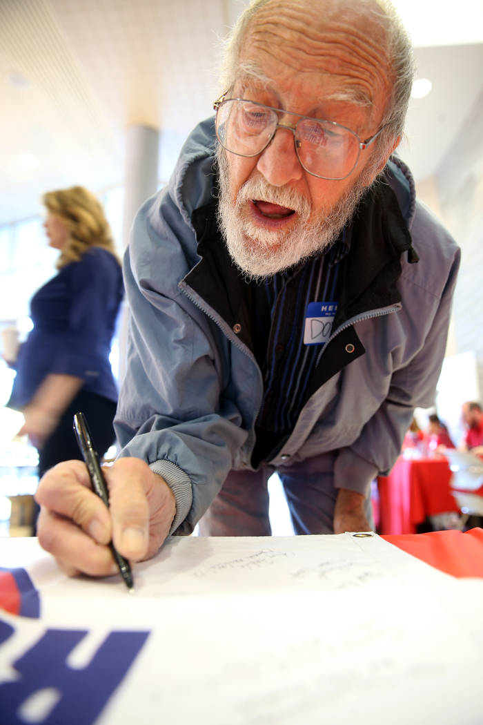 Donald Miller, 79, of Las Vegas signs a banner during the Cold War Patriots National Day of Rem ...