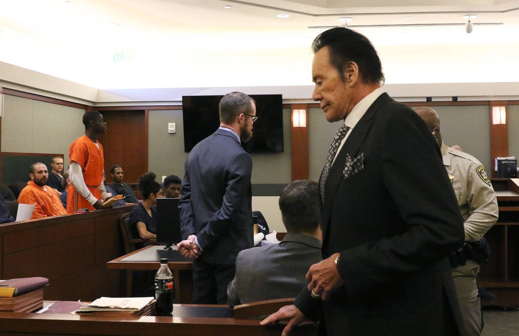 Wayne Newton, right, gets back to his seat after delivering his victim impact statement to the ...