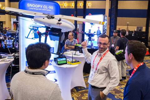 Eric Torres, middle, with Innoflight Technology, discusses the Snoopy CL-90 drone during the Co ...