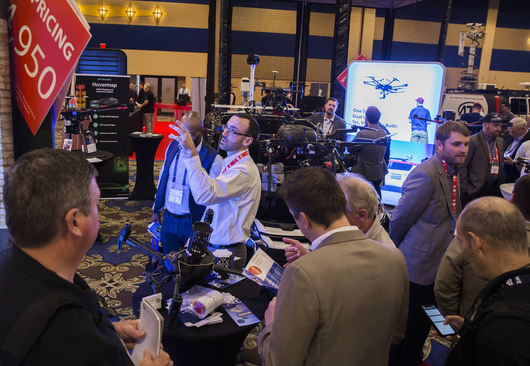 Eric Torres, third from left, with Innoflight Technology, discusses his company's line of produ ...