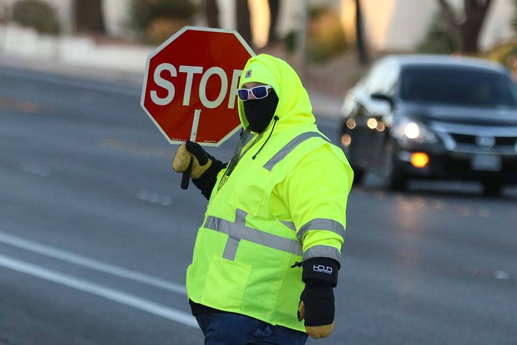 Crossing guard Paul Kotoch bundled up against the cold as he he directs traffic on Wednesday, O ...