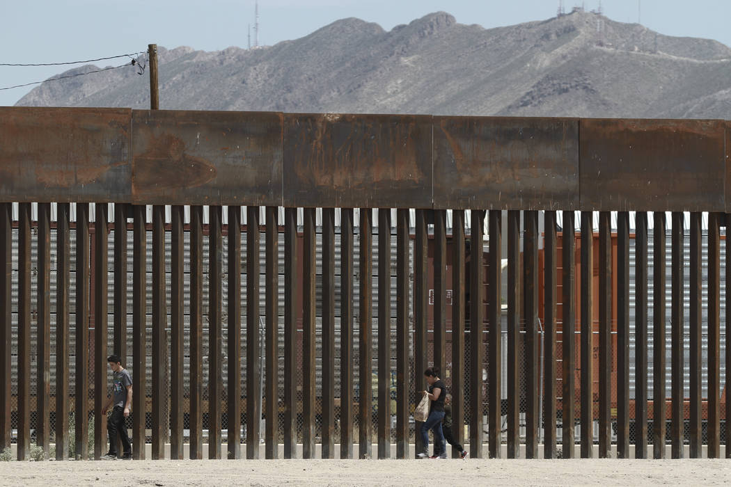 FILE - In this July 17, 2019 file photo, three migrants who had managed to evade the Mexican Na ...