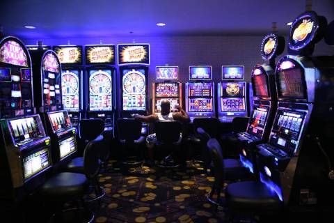 A person sits in front of a slot machine at the D Las Vegas hotel-casino in Las Vegas, Friday, ...