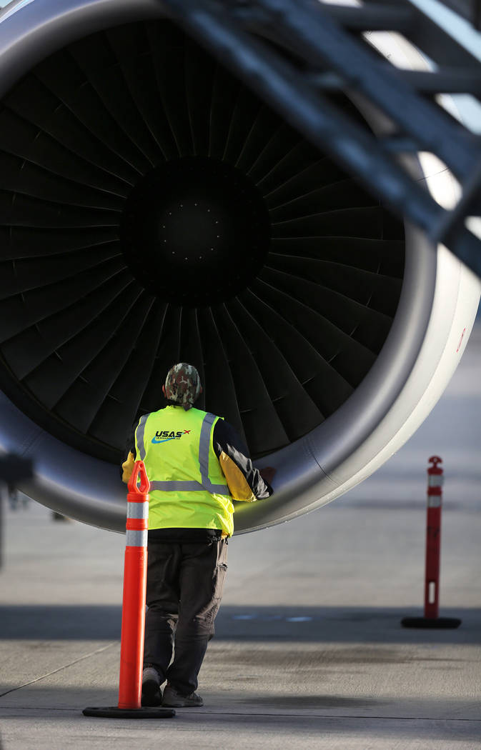 An airline worker inspects the engine of Level's first non-stop transatlantic service between P ...