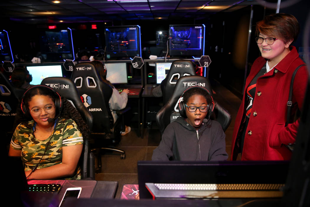Yzzi Ocampo, right, team manager with 8-bit Esports, right, watch eighth graders Jaelina Richar ...