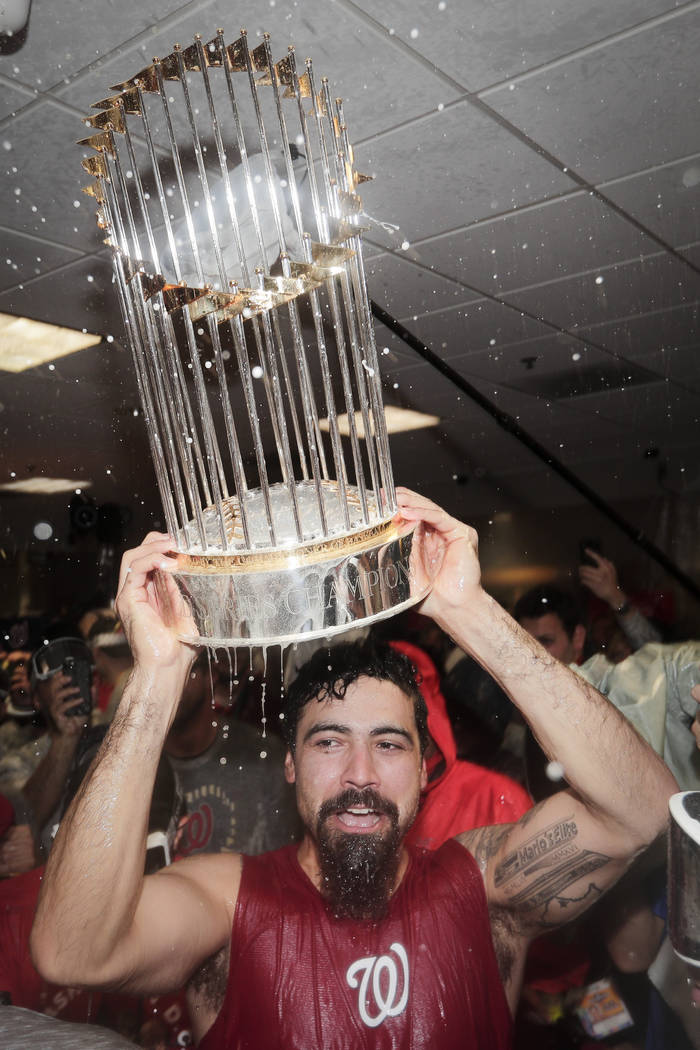 Washington Nationals third baseman Anthony Rendon celebrates with the trophy in the locker room ...