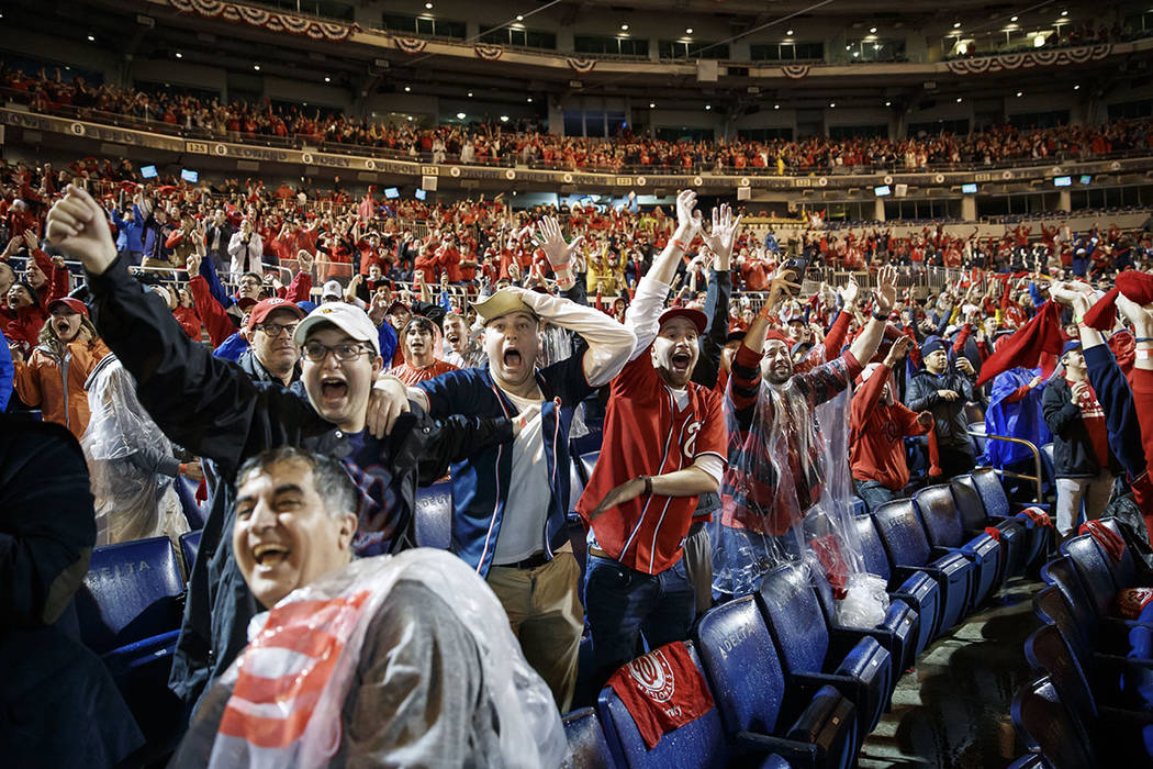 Washington Nationals fans celebrate at Nationals Park in Washington while watching television c ...