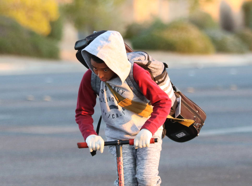 A boy is bundled up against the cold as he rides his scooter on Wednesday, Oct. 30, 2019, in He ...