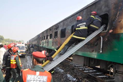 Rescue workers look for survivors following a train damaged by a fire in Liaquatpur, Pakistan, ...
