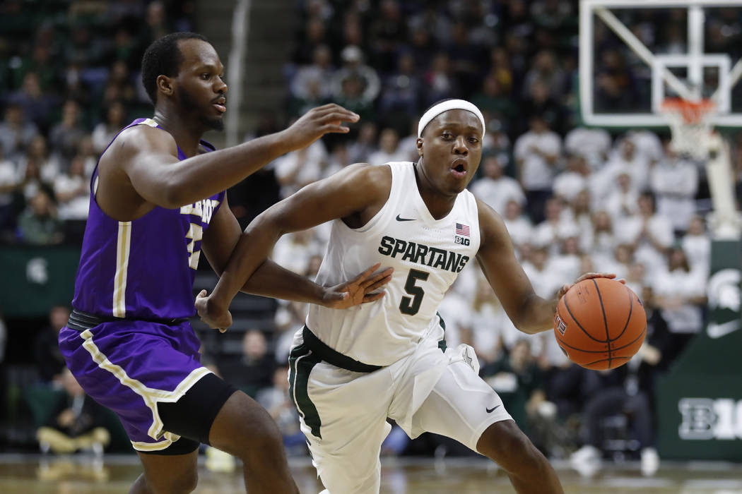 Michigan State guard Cassius Winston (5) drives on Albion forward Quinton Armstrong during the ...