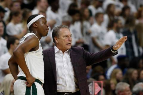 Michigan State head coach Tom Izzo talks with guard Cassius Winston during the first half of an ...