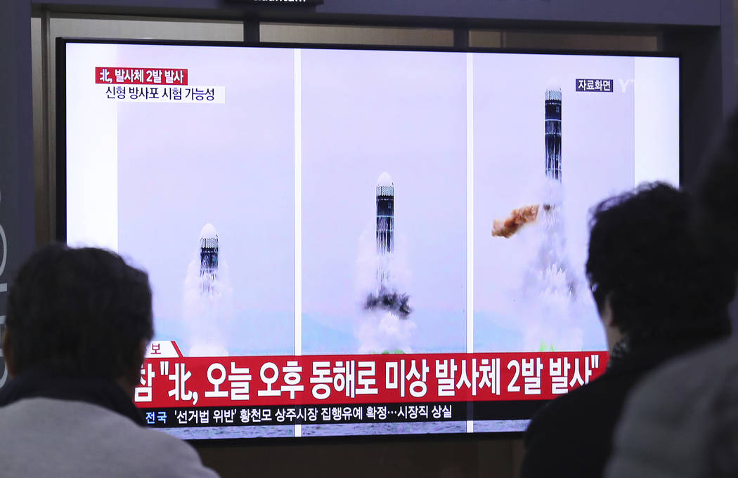 People watch a TV showing file images of North Korea's missile launch during a news program at ...