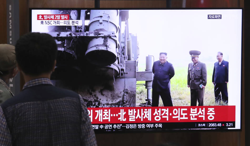 People watch a TV showing a file image of North Korean leader Kim Jong Un during a news program ...