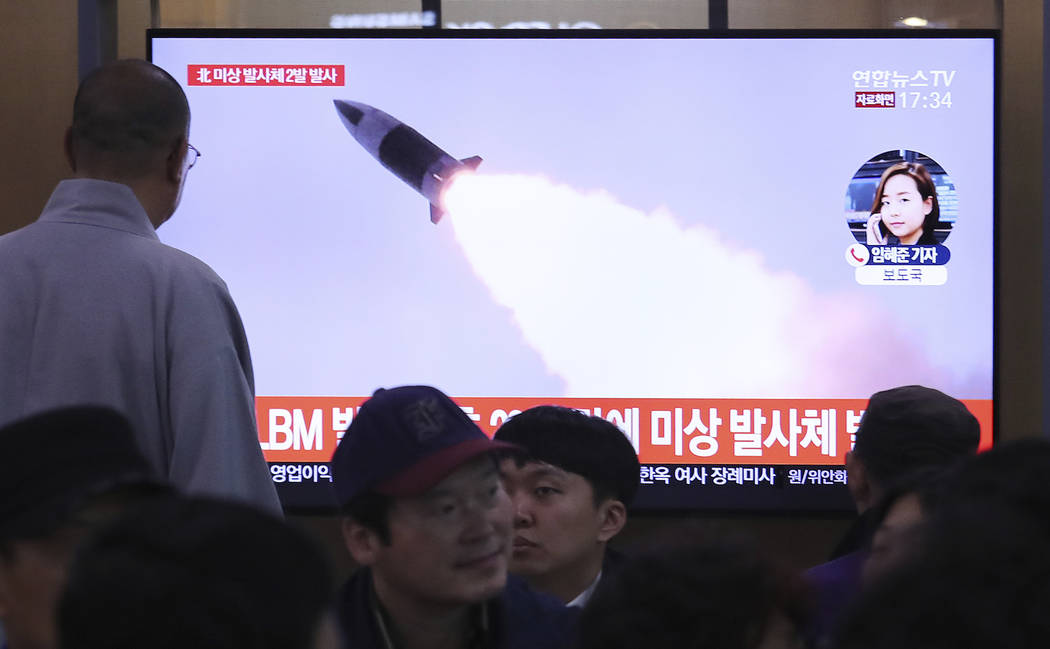 People watch a TV showing a file image of North Korea's missile launch during a news program at ...