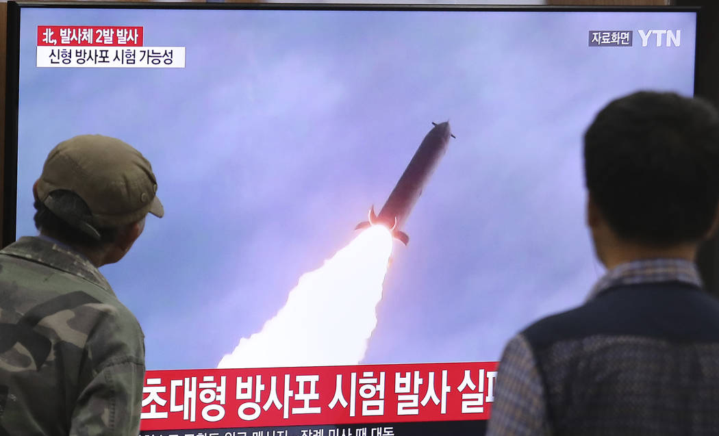 People watch a TV showing a file image of an unspecified North Korea's missile launch during a ...