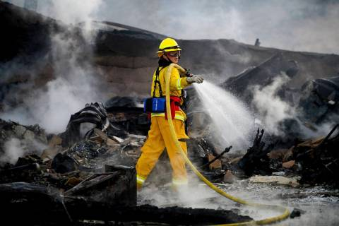 A firefighter sprays water on a leveled home as the Hillside Fire burns in San Bernardino, Cali ...