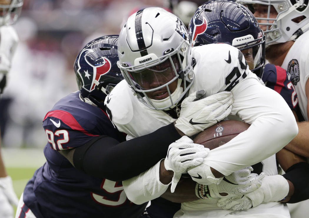 Oakland Raiders running back Josh Jacobs (28) is hit by Houston Texans nose tackle Brandon Dunn ...