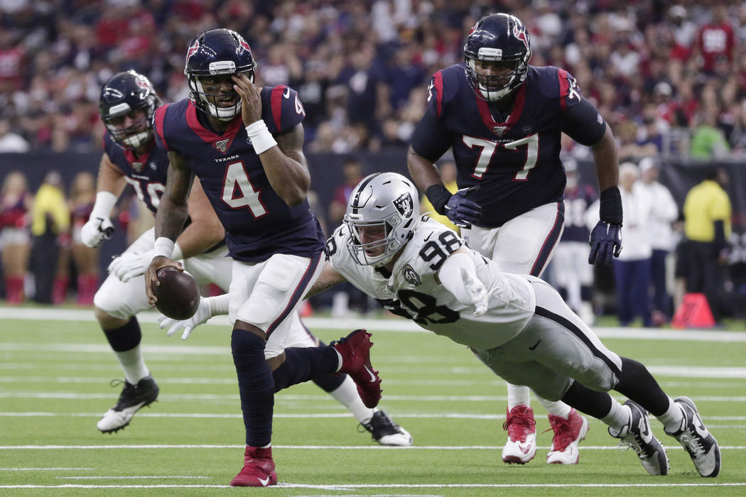 Houston Texans quarterback Deshaun Watson (4) holds his eye as he is pressured by Oakland Raide ...