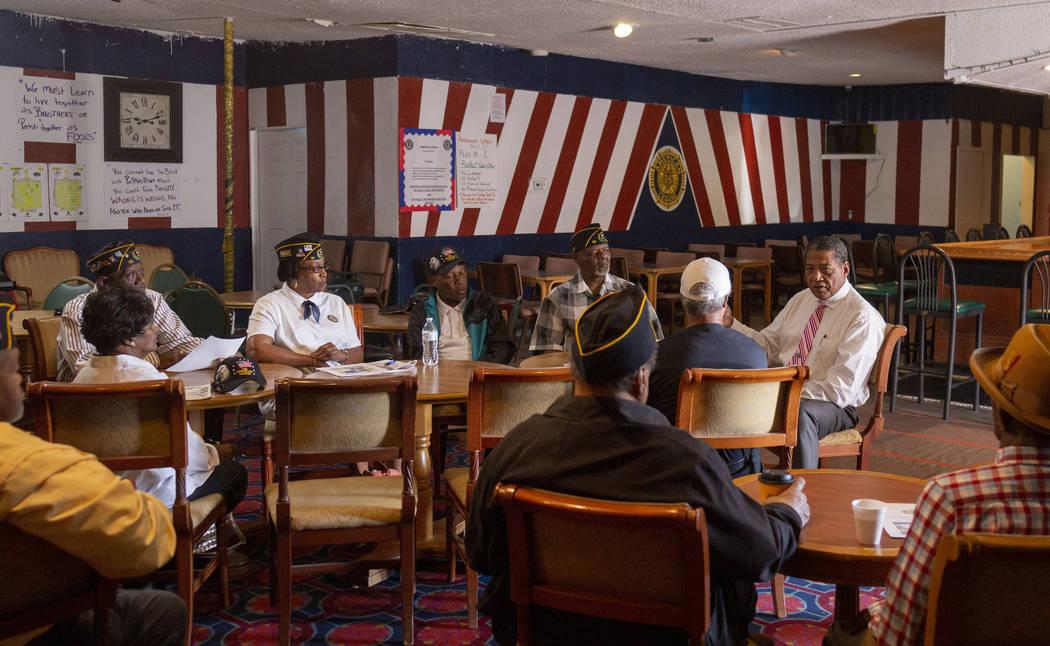 Veterans Program Director at American Legion Post 10 Commander Grady Hayes, background right, s ...