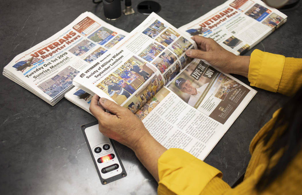 Su Phelps, publisher of the Veterans Reporter News, holds a copy of the publication as she spea ...