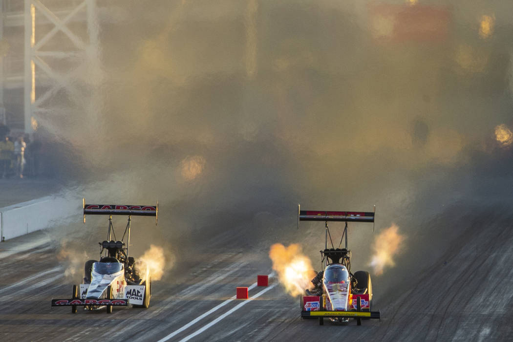 Top Fuel racers Steve Torrence and Brittany Force stay close during the final round of the Dodg ...