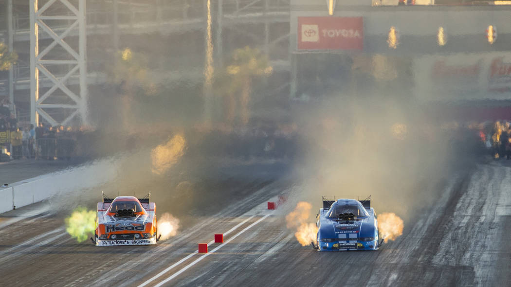 Funny car racers Jonnie Lindberg, left, and Matt Hagan battle in the final round during the Dod ...