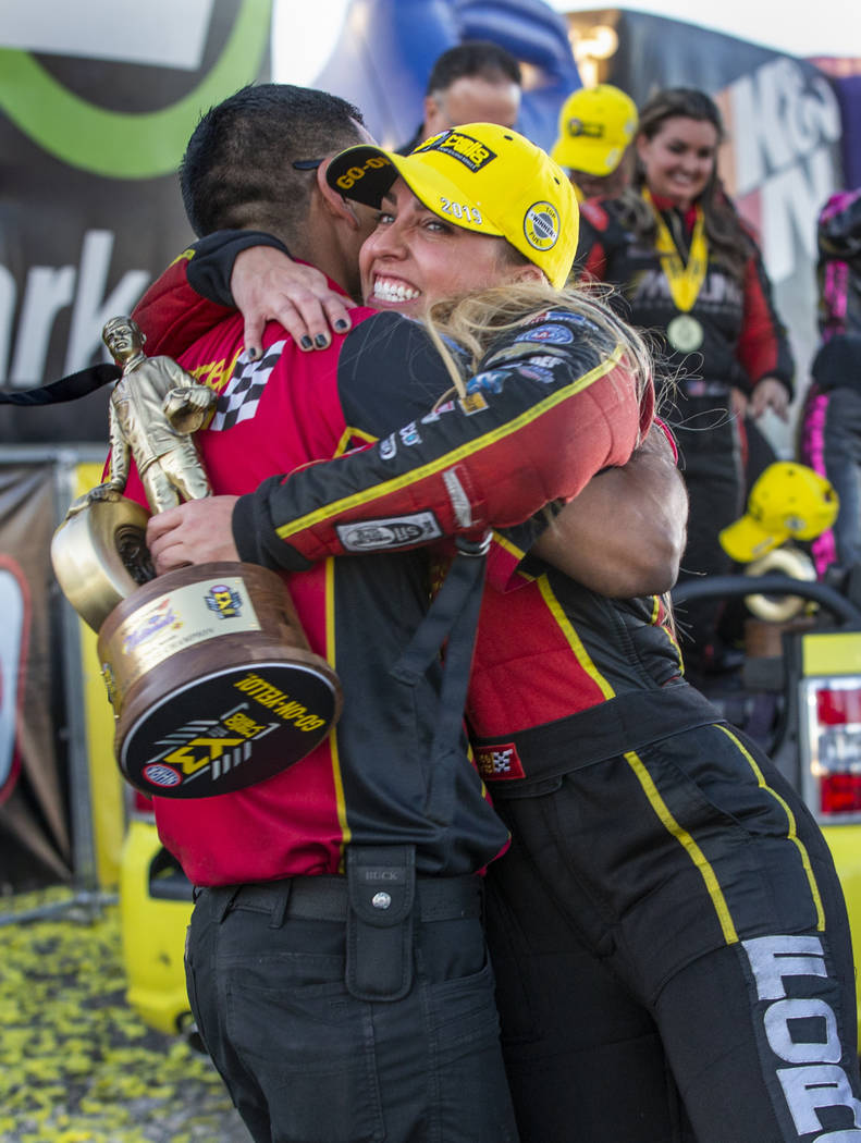 Top Fuel race winner Brittany Force, left, hugs crew member Narciso Bravo while carrying her tr ...