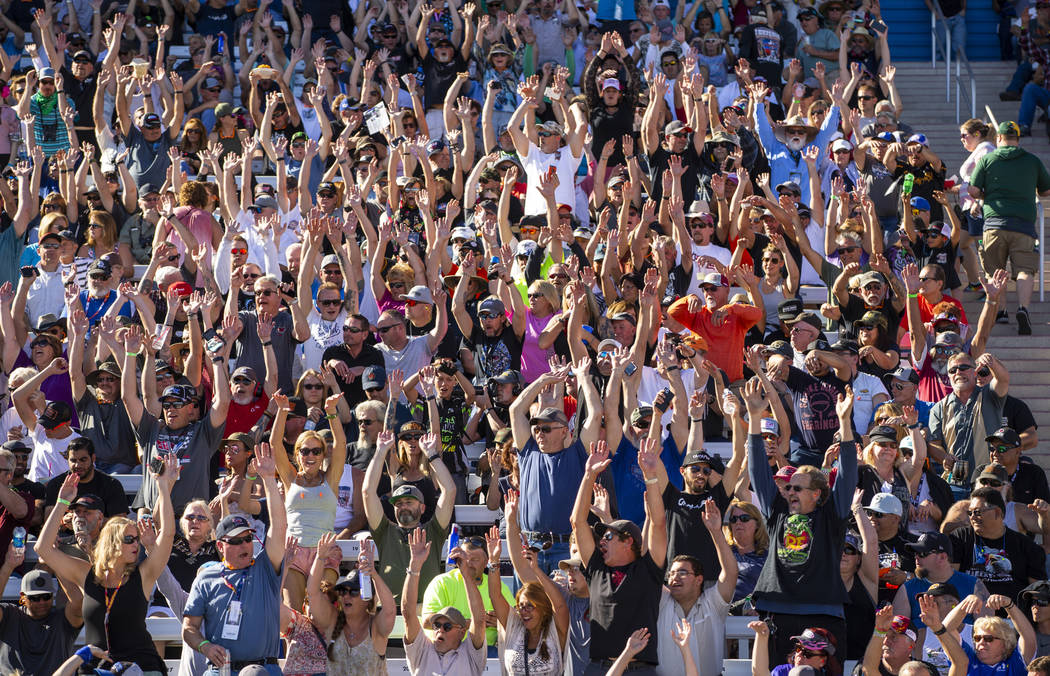 """Fans stand and do the """"wave"""" during the second round of the Dodge NHRA Nationals at t ..."""