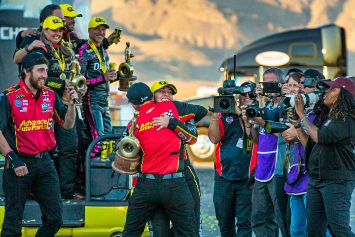 Top Fuel race winner Brittany Force hugs a crew member while carrying her trophy following the ...