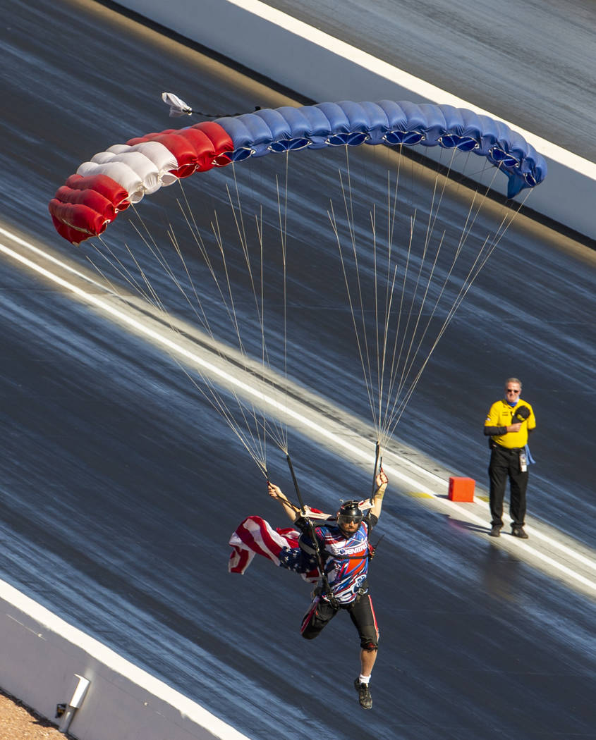 A skydiver delivers the American flag before the National Anthem during the Dodge NHRA National ...
