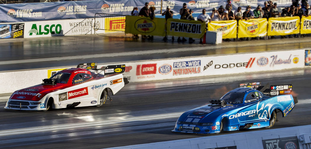 Funny car racers Bob Tasca III, left, and Matt Hagan battle for the lead in the second round du ...