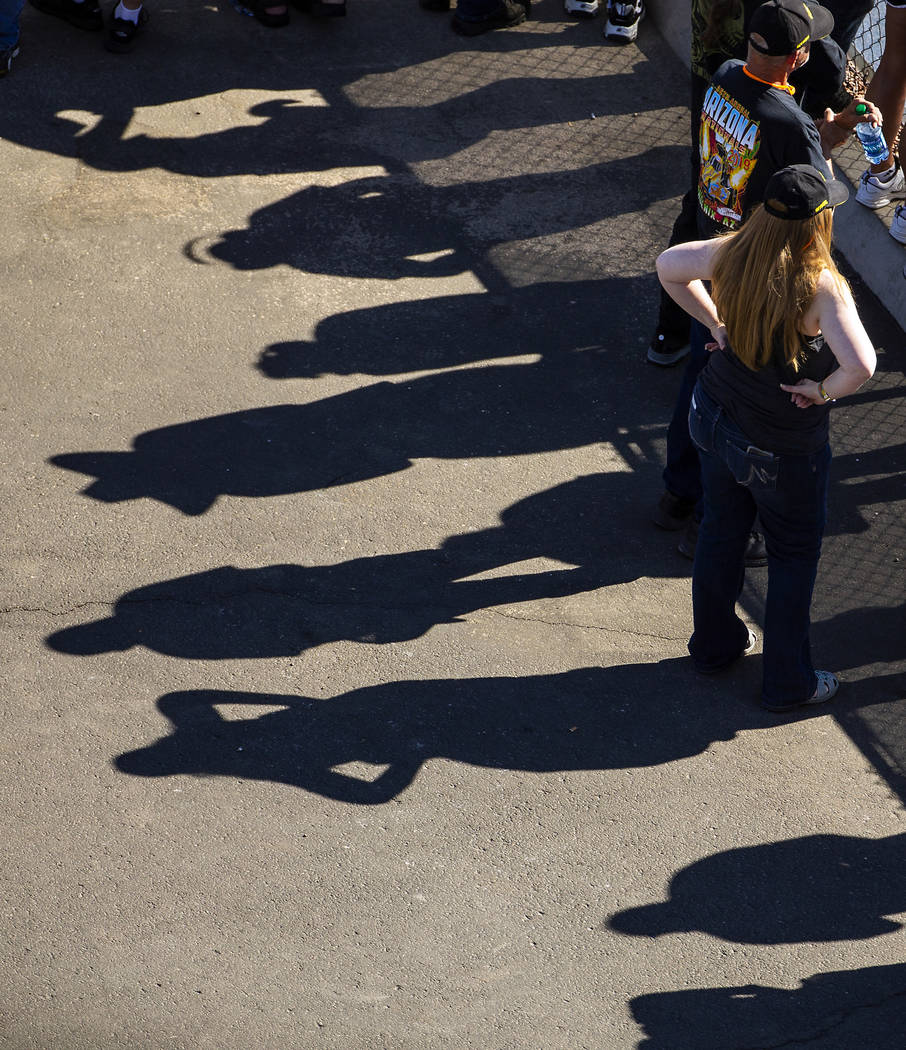 Shadows of fans are reflected on the pavement during the Dodge NHRA Nationals at the Las Vegas ...