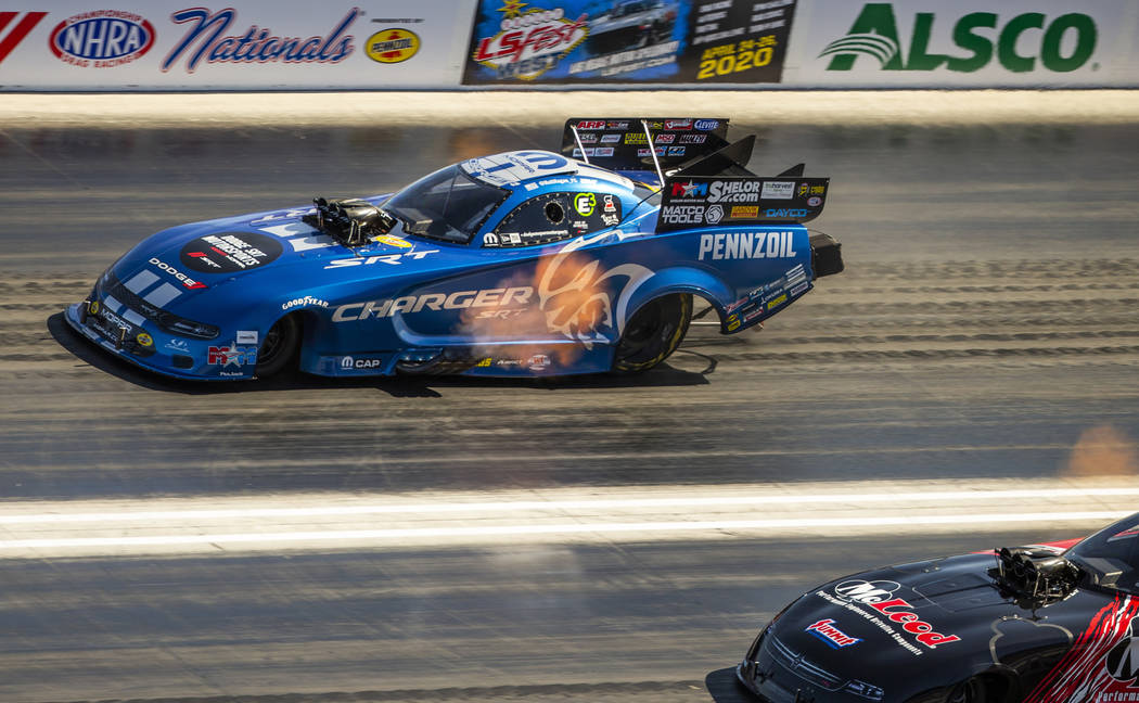 Funny car racer Matt Hagan, above, takes the lead in the first round during the Dodge NHRA Nati ...