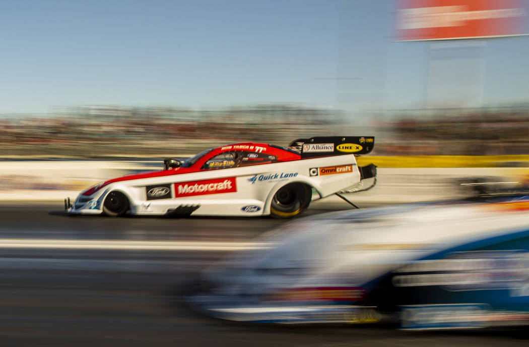 Funny car racer Bob Tasca III, left, takes the lead in the second round during the Dodge NHRA N ...