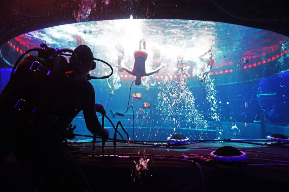 """A diver technician, left, supplies oxygen to synchronized swimmers performing """"Tango."""" Dur ..."""