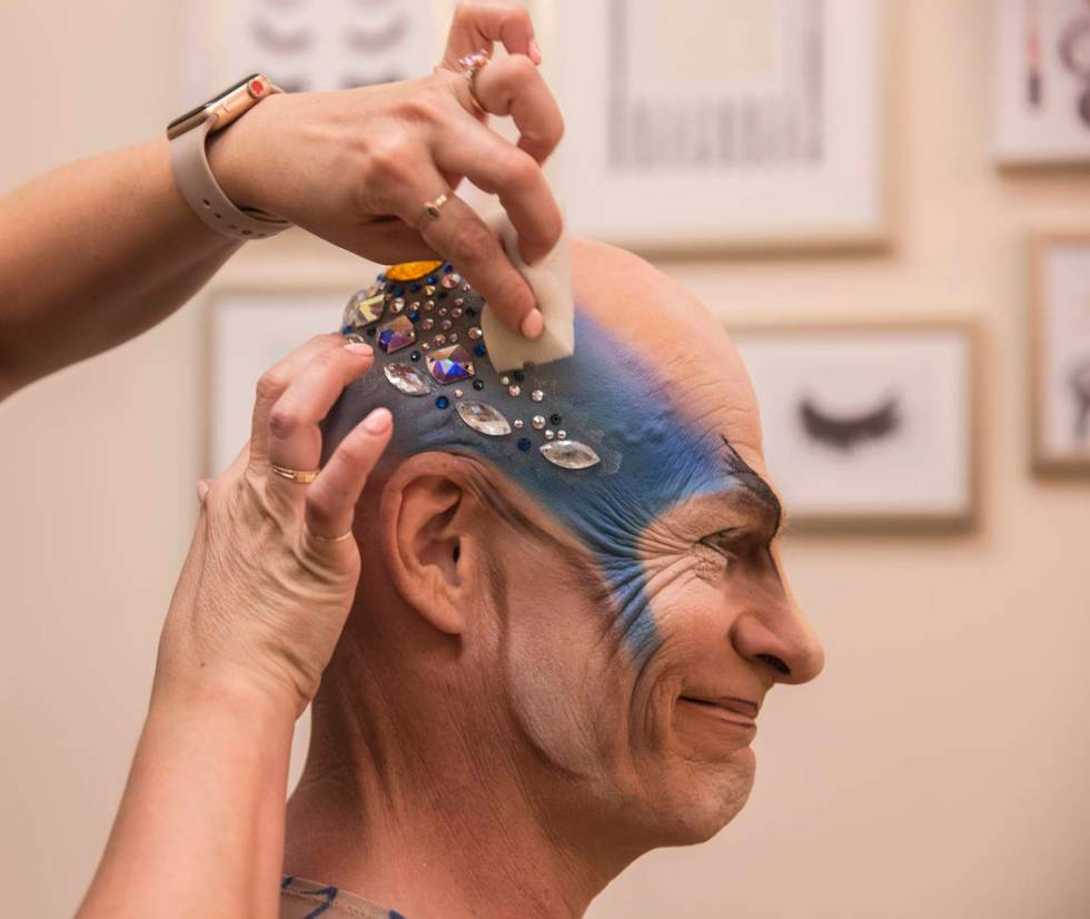 Performer and coach Didier Antoine gets his makeup applied to play the role of Morpheus before ...